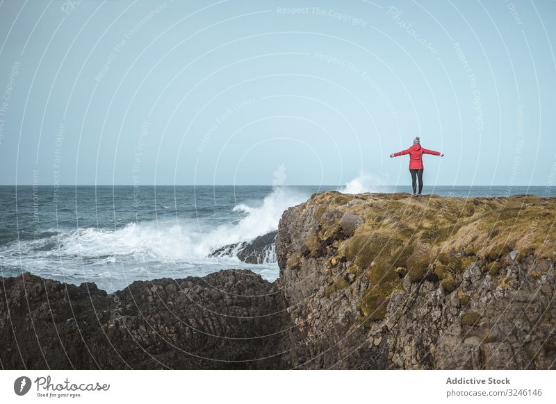 Woman on top of rock with sea surf woman cliff edge raging stormy splash coast water waves blustering crag marine highland climb female ballintoy antrim