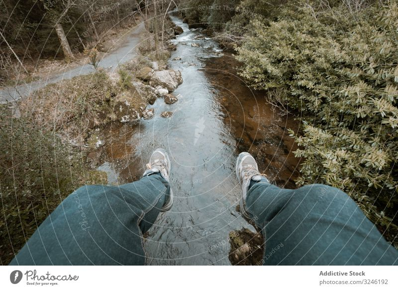 Tourist sitting on bridge and dangling legs over river tourist hang forest ireland park tollymore hiker person active walk nature landscape stream scenic