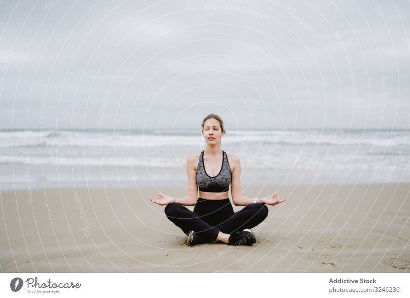 Woman meditating on the beach woman yoga practice sea ocean female exercise training workout young athlete active calm tranquility sportswear body fitness