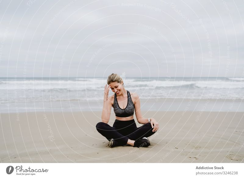 Woman meditating on the beach woman yoga practice sea ocean female exercise balance training workout young athlete active calm tranquility sportswear body