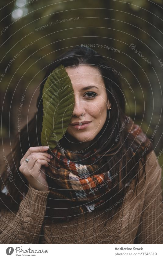 Woman covering eye with leaf woman forest covering eyes stylish nature scarf sweater casual female relax season plant part warm brunette lifestyle foliage
