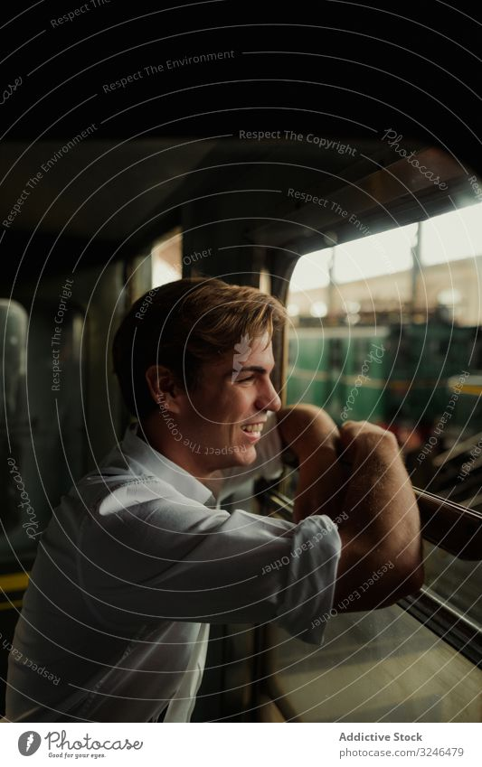 Cheerful traveler looking out train window man smile station railway rest stop transport male young retro vintage railroad trip journey commute vehicle public