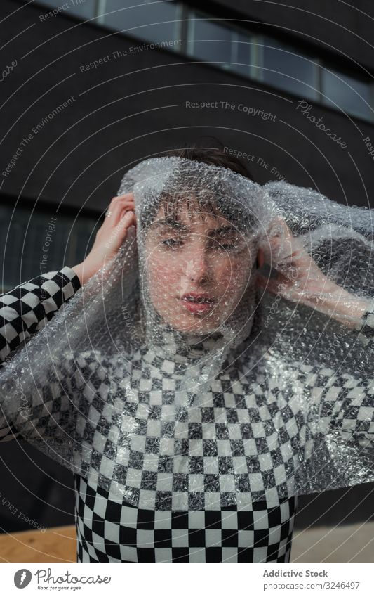 Fashionable woman in trendy casual wear in bubble wrap at city street fashion stylish teenager female hipster wrapping hidden outfit model beauty young vogue