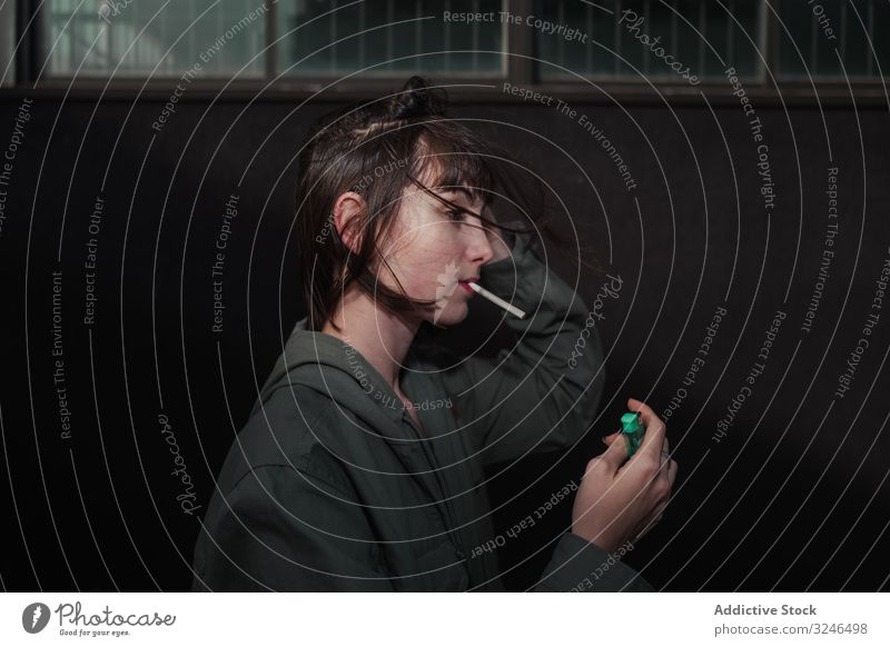 Female teenager in casual clothing smoking cigarette at city street light up holding liter wear jacket outfit grey wall nail blue brunette rebel sad modern