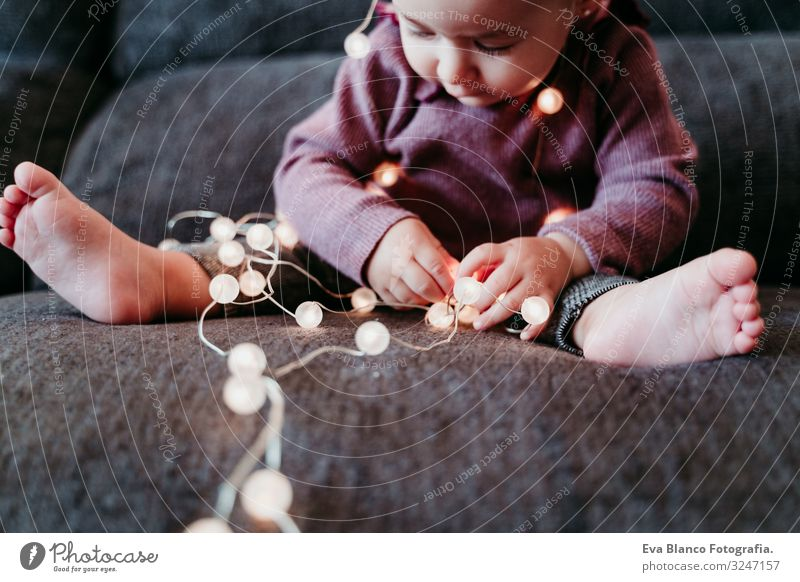 portrait of beautiful baby girl at home sitting on the sofa playing with a garland of lights Lifestyle Joy Happy Leisure and hobbies Playing Flat (apartment)
