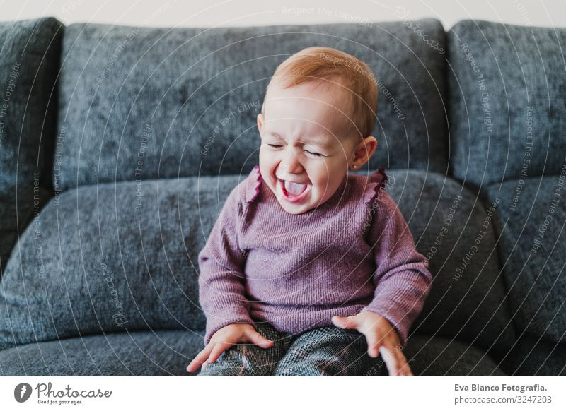 beautiful baby girl laughing at home sitting on the sofa Lifestyle Joy Happy Leisure and hobbies Playing Flat (apartment) House (Residential Structure) Sofa