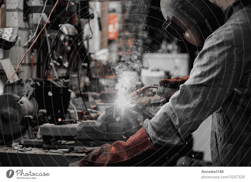 welder is welding metal part in garage. with protective mask, Work and employment Profession Workplace Factory Industry Tool Technology Man Adults Metal Steel