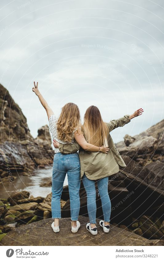 Young sisters standing on stone on spring day women embrace nature hill mountain countryside together female friends love hug support friendship relationship
