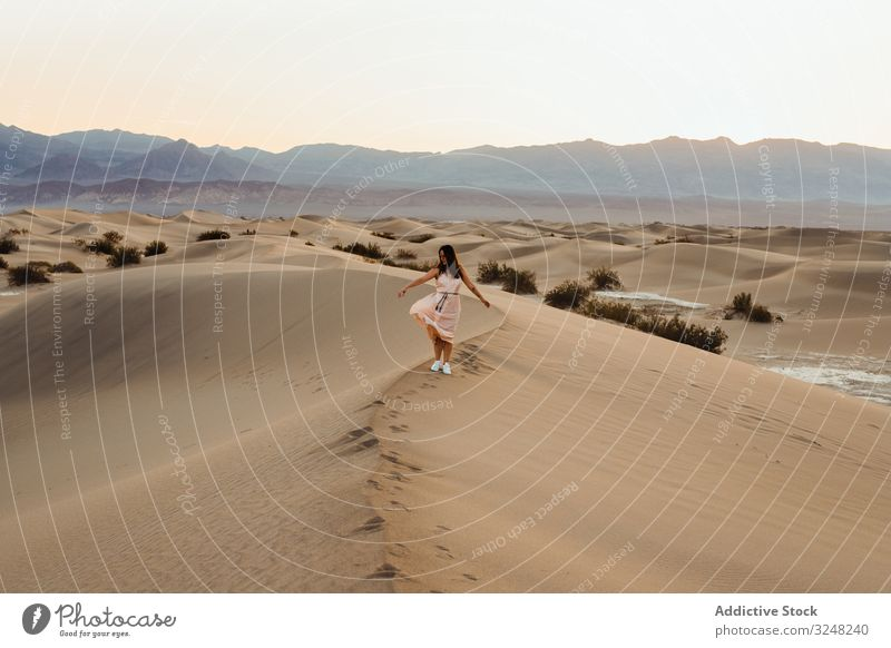 Back view of young woman walking in desert leaving footprints in dry sandy dunes in Death Valley death valley wanderlust travel vacation direction holiday