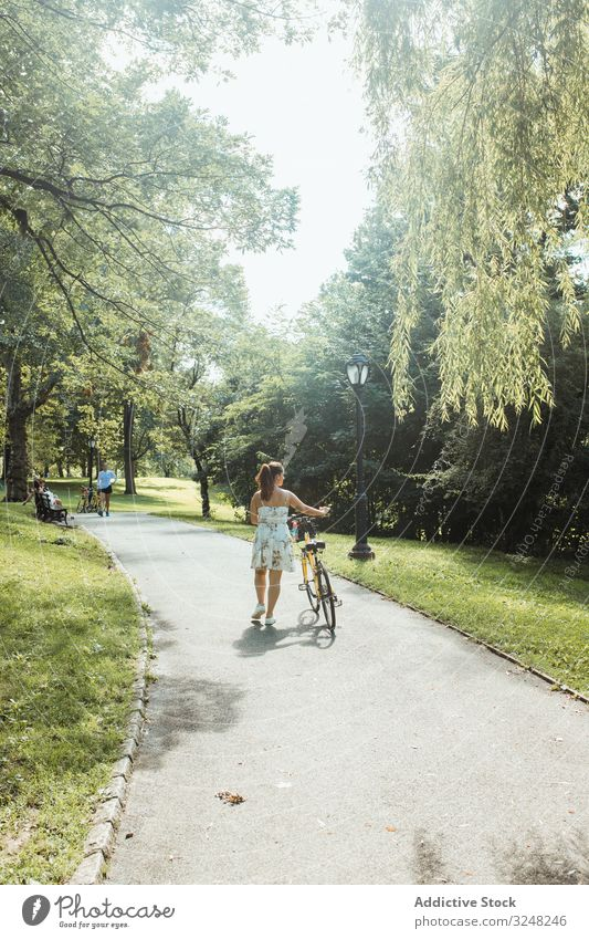 Casual lady wheeling bicycle at beautiful park woman walking summer sunlight casual dress female activity lifestyle sport road transport weekend carefree