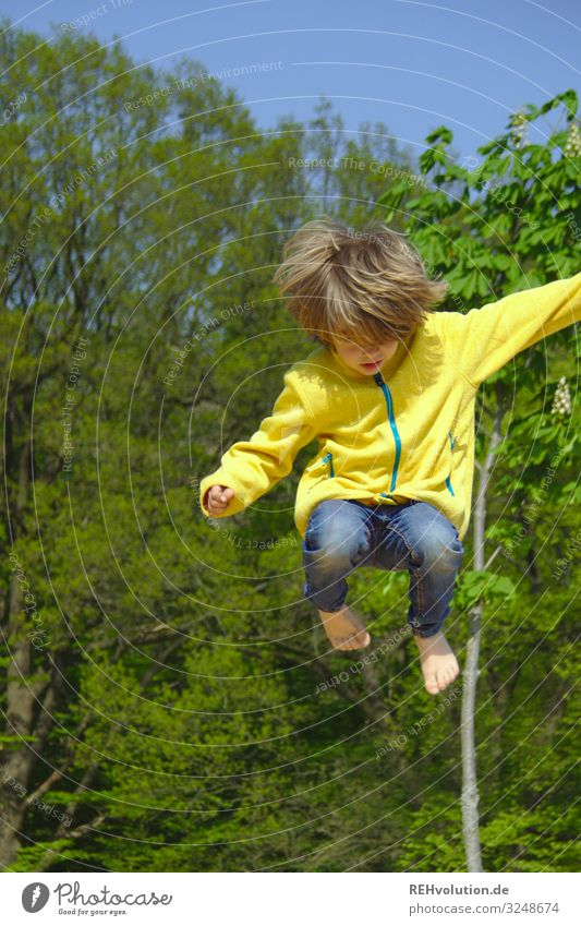 child jumps up Jump Dynamic Movement active Tall Athletic Sports Playing Playground Yellow green huts Barefoot fun Trampoline Boy (child) Jacket Summer Hop Joy