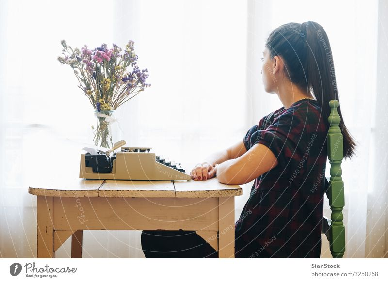 Young woman typing on a vintage typewriter Work and employment Office Hand Paper Metal Old Write Retro Nostalgia Antique Writer background equipment girl
