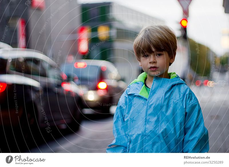 Child standing on a street Street Road traffic Traffic light Transport Town Boy (child) peril Responsibility way to school Going Traffic infrastructure