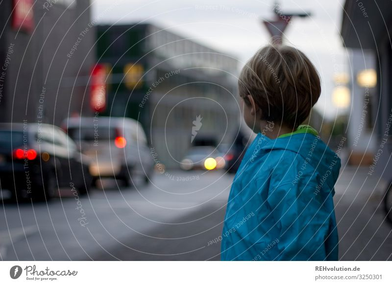Boy stands by the road Dreary Bad weather clearer Light Passenger traffic Means of transport Downtown Vehicle Crossroads Colour photo Pedestrian Motoring