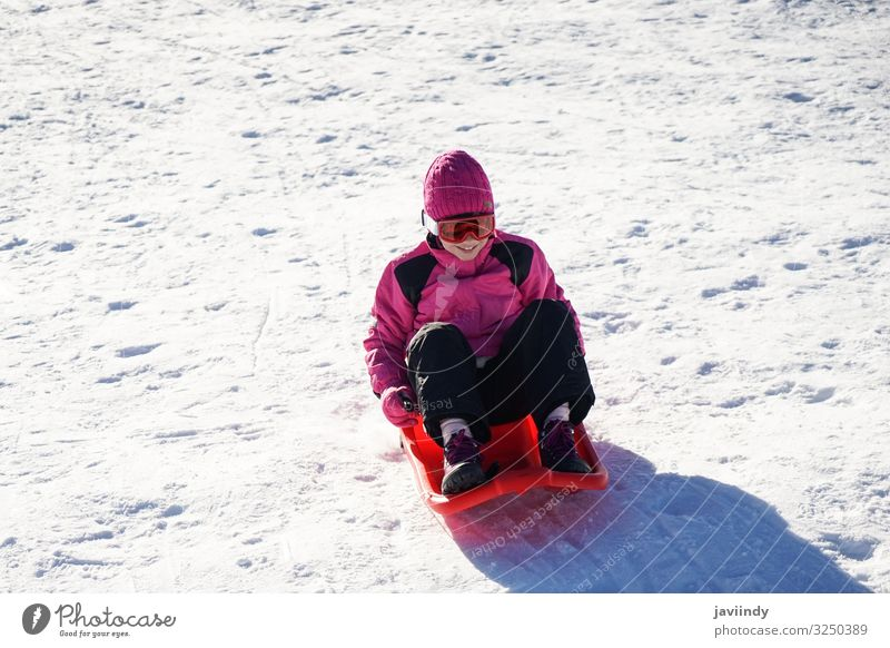 Little girl sledding at Sierra Nevada ski resort. Joy Happy Relaxation Leisure and hobbies Playing Vacation & Travel Winter Snow Mountain Sports Child