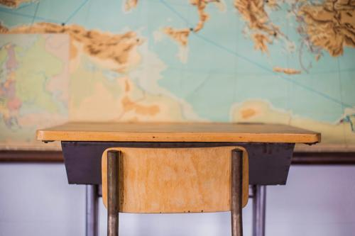 Empty desks at school classroom with world map. House (Residential Structure) Furniture Desk Chair Table Adult Education Child School Classroom Blackboard