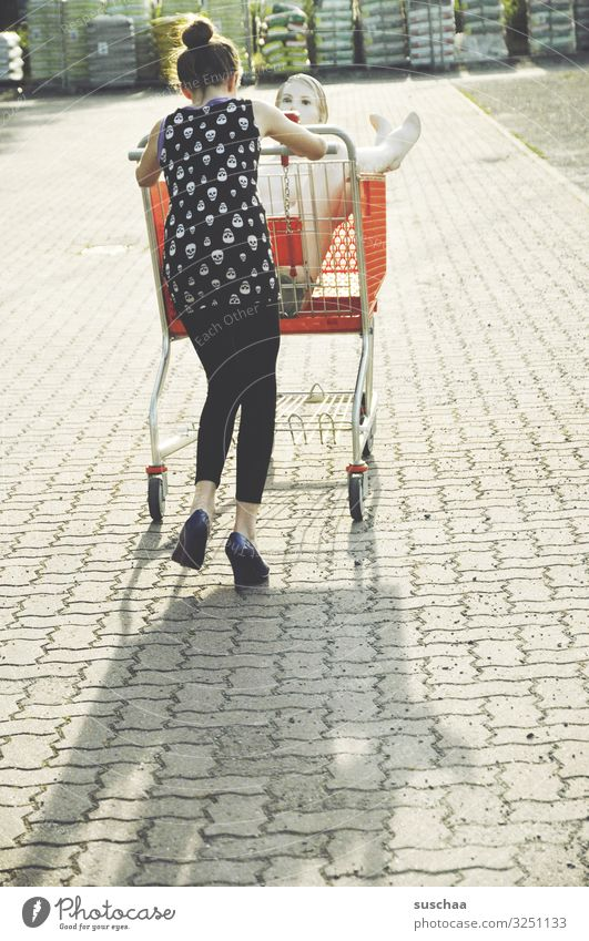 Child Youth (Young adults) Young woman Summer Town Joy Girl Funny City life Shopping To go for a walk Whimsical Strange Parking lot Mannequin Shopping Trolley