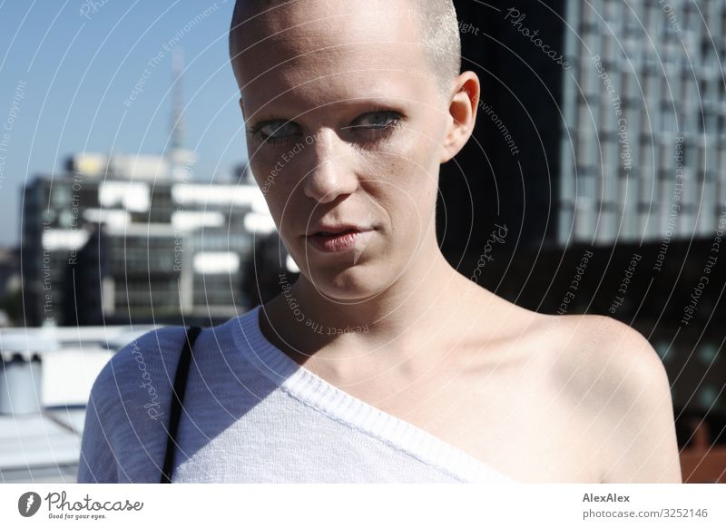 Portrait of a young, bald woman standing on a roof in Hamburg, so that you can see the skyscrapers of Hamburg in the background. pretty Life Young woman