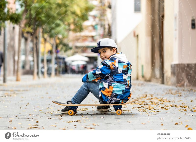 Cute little kid sitting on his sakteboard Child Human being Vacation & Travel Blue Town Colour Beautiful Loneliness Joy Winter Street Lifestyle Sports Happy