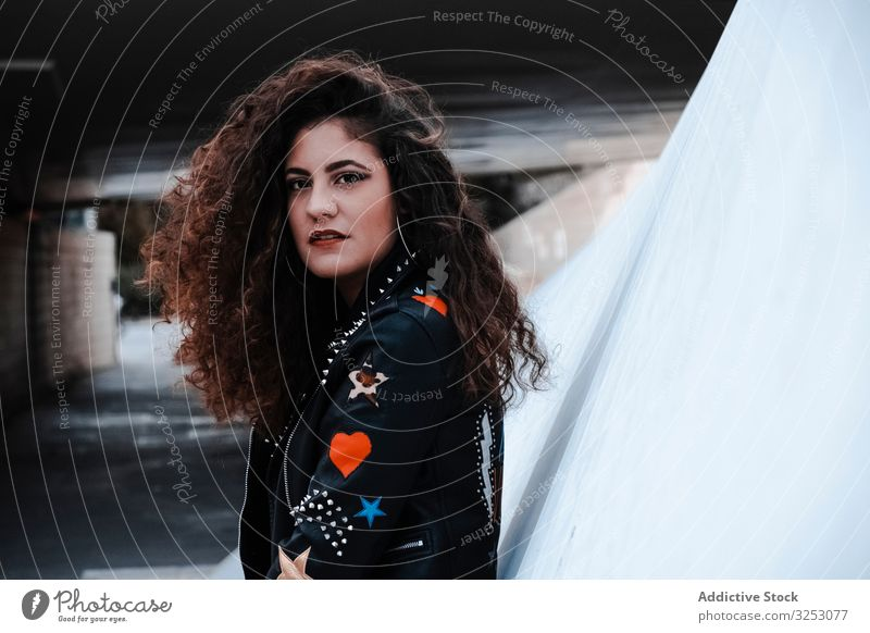 Young woman in rocker outfit looking at camera style jacket leather black stripes brunette fashion urban city long hair young female street wavy hair trendy