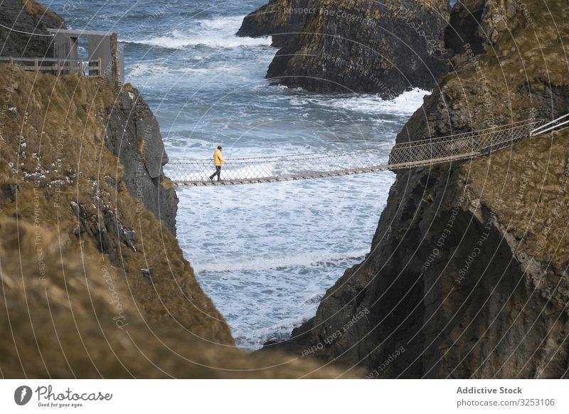 Tourist walking on rope bridge suspended between cliffs in Northern Ireland rock sea tourist ocean northern ireland person cross coast shore water landscape