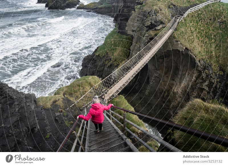 Woman crossing rope bridge leading to rocky island woman sea walk ocean northern ireland coast carric a rede shore water landscape female confidence courage