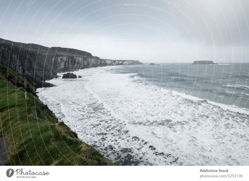 Northern Ireland coastline with waves ocean seascape stormy cloudy rock grass foam northern ireland landscape weather cold grey season power energy mountain