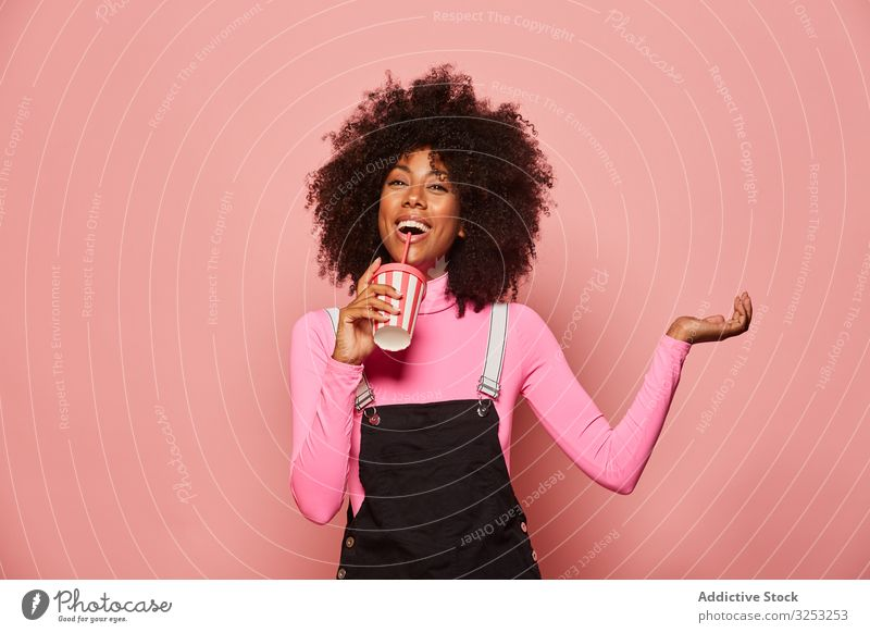 Happy black woman with disposable cup of drink standing against pink background happy straw african american laugh cheerful gesture ethnic female young casual