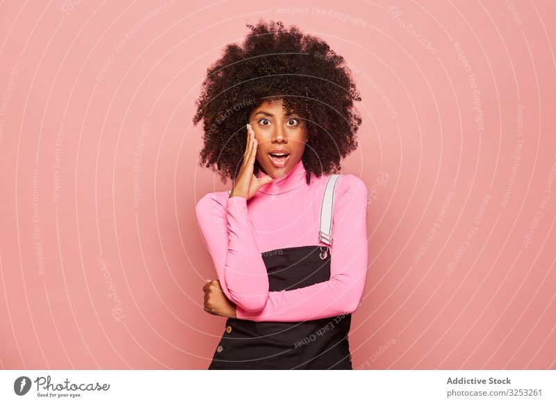 Shocked African American woman looking at camera surprised amazed shocked young casual pink african american black stand female ethnic turtleneck overall