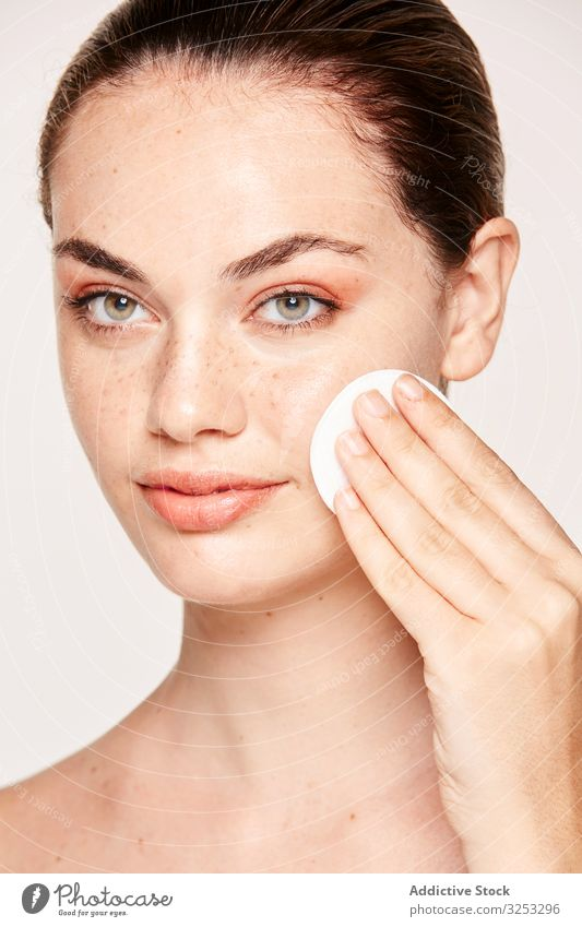 Peaceful female applying toner on radiant face with sponge woman cleanse lotion gel skin freckle peaceful cure mask renewal wrinkle care facial beauty treatment
