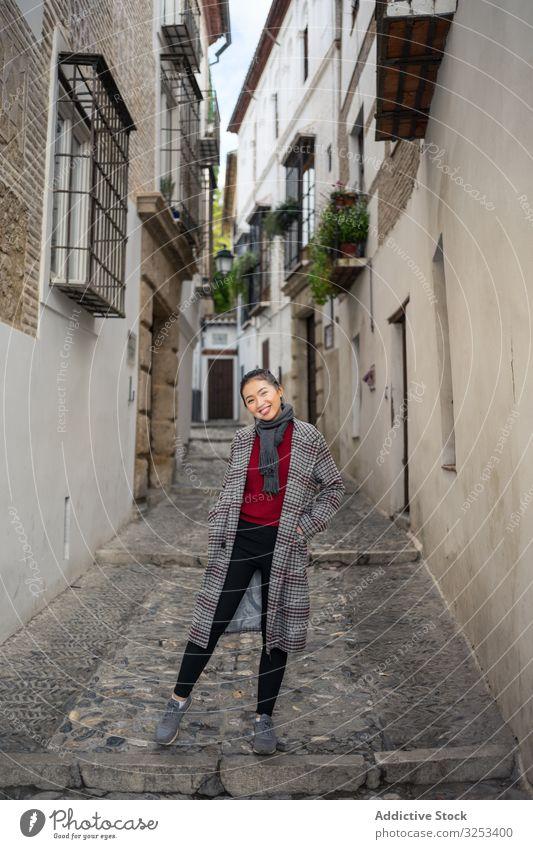 Joyful female tourist in casual wear amid city street woman travel walk explore smile lane enjoy young holiday lifestyle adventure vacation albaicin granada