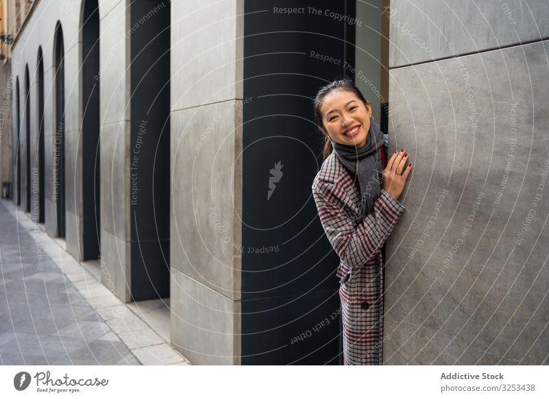 Joyful Asian resting female in casual clothing looking out modern wall of building at city street woman travel town tourist door peer peek playful exploring fun