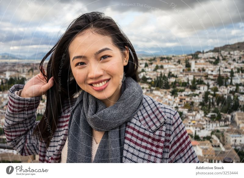 Cheerful ethnic woman visiting ancient city tourism cloudy sky smile female stylish trendy architecture asian travel trip happy cheerful overcast delighted