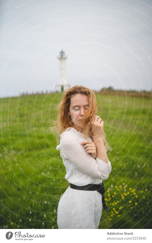 Tender woman in green field with lighthouse tender meadow gentle charming calm peaceful redhead ginger scenic nature asturias spain europe sensual silent serene