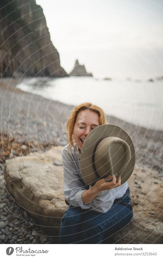 Woman resting on beach stone by sea woman bay water seascape coast shore rock calm contemplate dreaming carefree tourist enjoy relax chill traveler distance