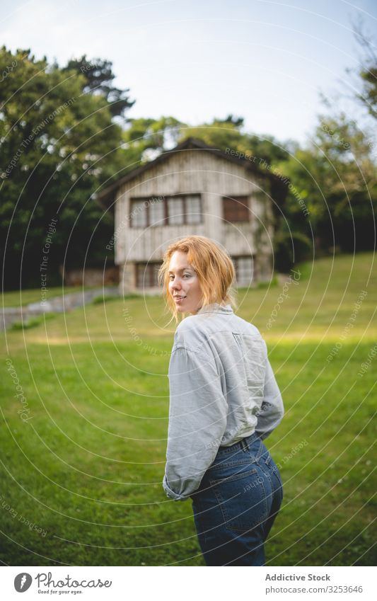 Content female walking on grass in countryside woman house enjoy field stroll meadow calm peaceful content thoughtful carefree rural village redhead ginger