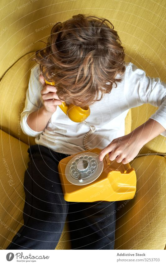Boy using telephone at home boy calling playing kid talking child male imagination communication connection conversation yellow sitting armchair living room