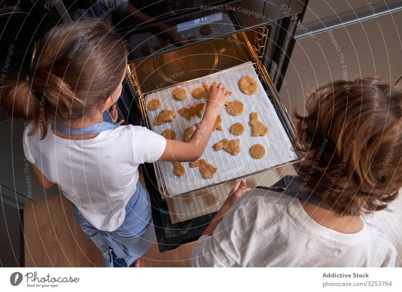 Little kids in aprons baking cookies at home oven sheet cooking together modern kitchen help study learn sweet fun preparation food enjoyment girl boy domestic