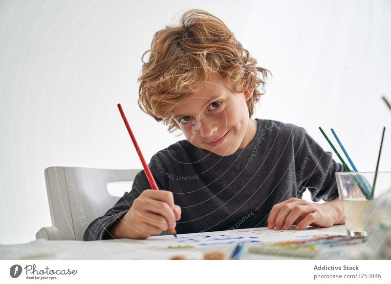 Cheerful boy painting and looking at camera smile paintbrush home art creative picture education table sit kid child tool craft study learn elementary