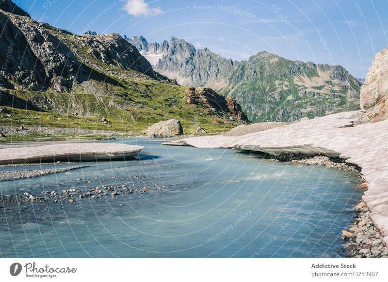 Shallow river flowing along rocky shore in bright day mountain water nature landscape sky scenic blue natural wilderness snow reflection switzerland grand