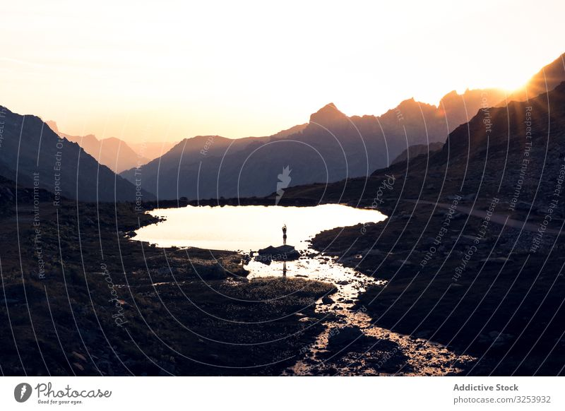 Person standing on shore and reflecting in water silhouette lake mountain reflection picturesque tranquil seaside stone sunset surface mirror landscape scenic