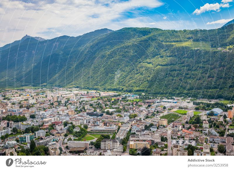 Densely populated town at foot of green mountains valley idyllic remote range small rocky landscape ridge stone architecture travel island structure nature road