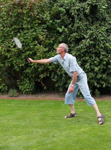 male senior plays badminton in the garden in summer Leisure and hobbies Playing Shuttlecock badminton rackets Fitness Sports Training Badminton Human being