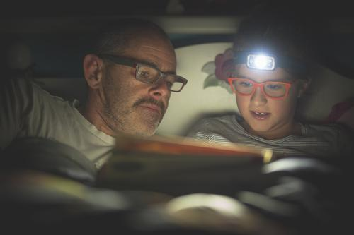 ..the light comes on Girl Father Adults Head 2 Human being Eyeglasses Moustache headlamp Discover Relaxation To enjoy Listening Reading Lie Looking Dark