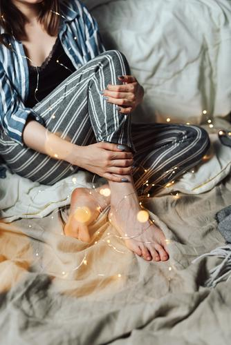 Woman sitting in her bed with Christmas fairy lights Evening Cozy Feasts & Celebrations Public Holiday Faceless pajamas Christmas & Advent hygge Fairy lights
