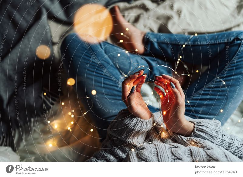 Woman sitting in her bed with Christmas fairy lights Human being Christmas & Advent Young woman Hand 18 - 30 years Lifestyle Bedclothes Jeans Home Denim Sweater