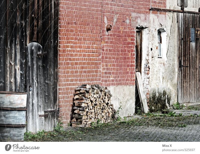 Wood in front of the hut Living or residing Flat (apartment) Village Deserted Old Farm Firewood Stack of wood Barn Barn door Brick wall Courtyard Colour photo
