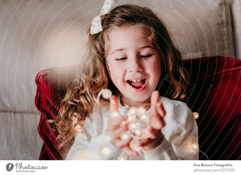 beautiful kid girl at home playing with garland of lights. Christmas concept Christmas & Advent Light Paper chain Home Blonde blue eyes Child Love Together