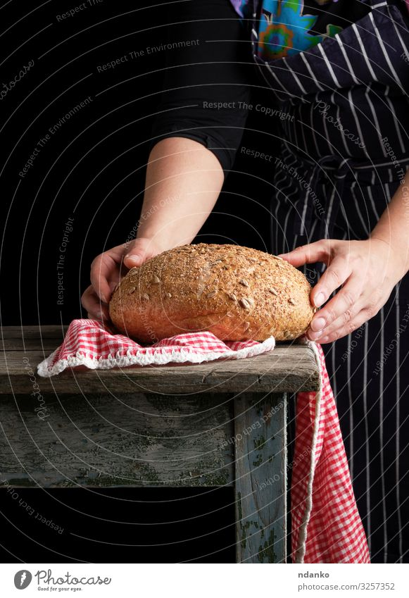 woman holds in her hands baked round rye bread Dough Baked goods Bread Table Kitchen Human being Woman Adults Hand Wood Make Dark Fresh Brown Red Black White