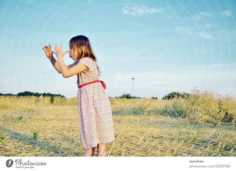 have a big nose Child Girl Dress Grain field Cornfield Summer straw field Exterior shot Warmth lateral view Hand have a long nose Gesture Brash Joke Funny